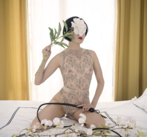 San Francisco and Oakland Asian Dominatrix Domina Yuki framed in a window with a leather whip and flowers.