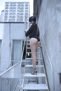 Asian Dominatrix Domina Yuki in stilettos looks back at the viewer while climbing stairs in Oakland.