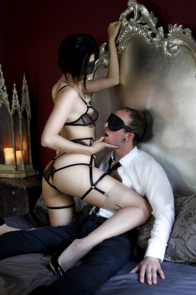 Grasping the headboard of a luxurious bed, Asian Femdom Domina Yuki caresses her male submissive's face.