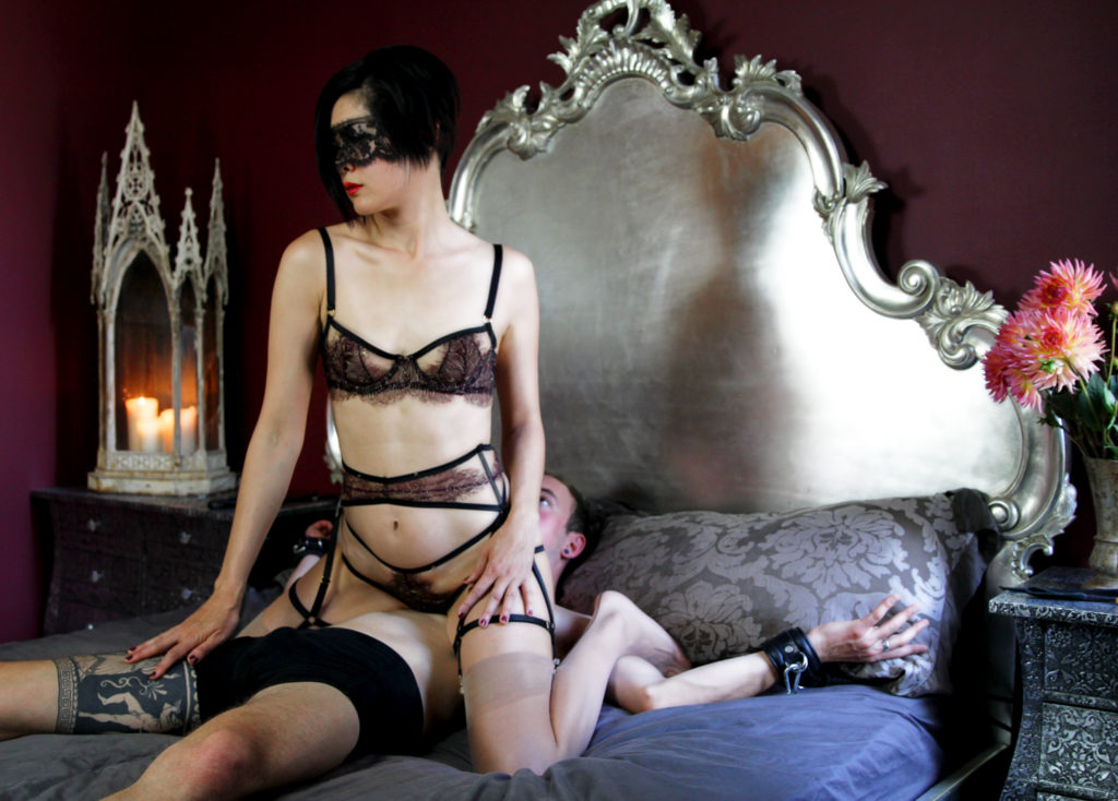 Professional Dominatrix Domina Yuki asserts her power by straddling and teasing her submissive bound to the bed.