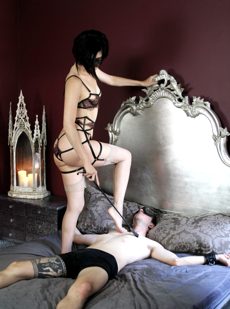San Francisco Dominatrix Domina Yuki places her foot on the chest of her male submissive bound to a luxurious bed.