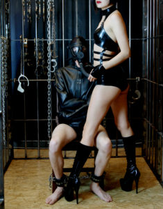 San Francisco Dominatrix Domina Yuki holds the face of her bound submissive who wears a gas mask and straitjacket.