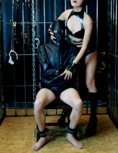 San Francisco professional dominatrix Domina Yuki asserts her power over her straitjacket bound male submissive.
