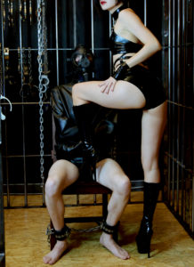 Asian Dominatrix Domina Yuki places her booted foot on her bound male submissive wearing a straitjacket and leg cuffs.