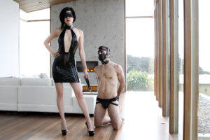 Asian Dominatrix Domina Yuki looking away while her male submission on a leash adores her.